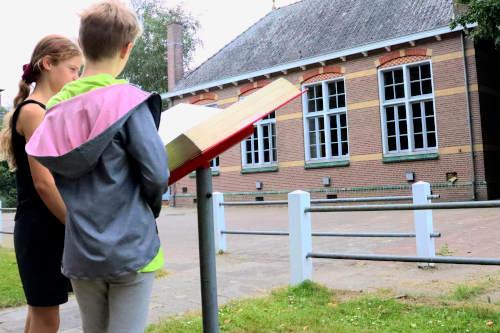 kinderen lezen informatiepaneel voor de oude school in het veenpark